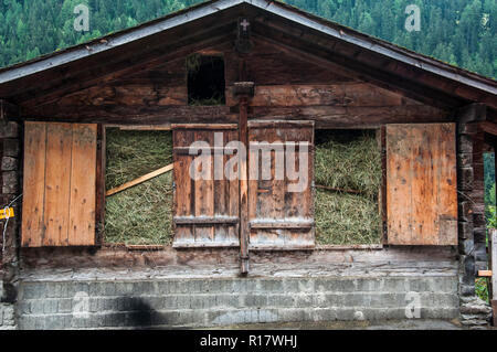 Traditional barn packed with fresh-cut fodder in the Loetschental Valley, Valais, Switzerland - Stock Photo