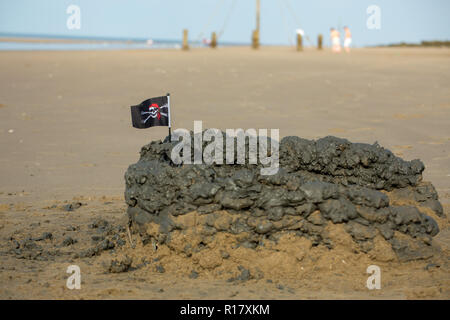 Sand castle/Mud castle and topped with a small skull & cross bones flag on the beach. Prestatyn, North Wales, UK, 2018 - Stock Photo