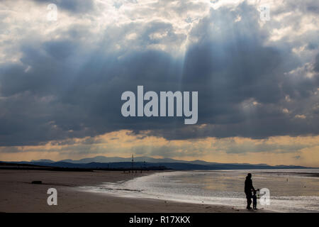 Empty beach on a gloomy moody day with sun beams coming through the stormy clouds.  Prestatyn and the mountains of Snowdonia are visible in the backgr - Stock Photo