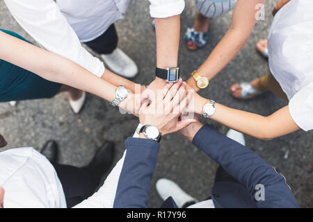 business, people and teamwork concept - smiling group of businesspeople standing in circle and putting hands on top of each other - Stock Photo