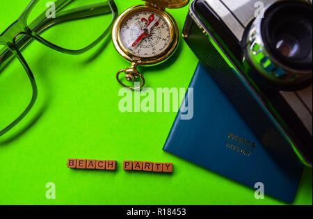 Beach party message written on wooden blocks,travel and vacation concept. passport, smartphone, eyeglass, analog camera isolated green background - Stock Photo