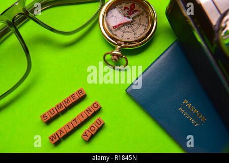 Summer waiting you message written on wooden blocks, passport, smartphone, eyeglass, analog camera isolated green background - Stock Photo