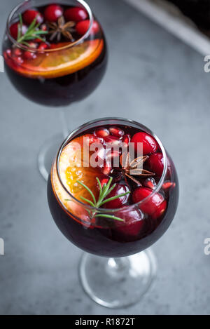 Christmas sangria with oranges, pomegranate seeds, cranberry, rosemary and spices - homemade festive drink mulled wine for Christmas time. - Stock Photo