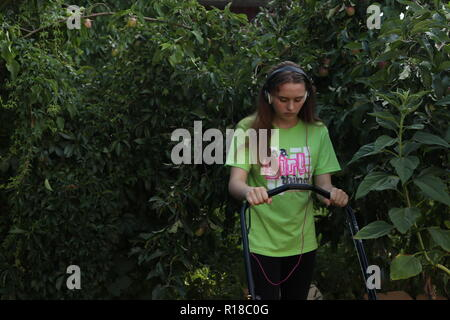 Girl who obviously hates mowing the lawn - Stock Photo