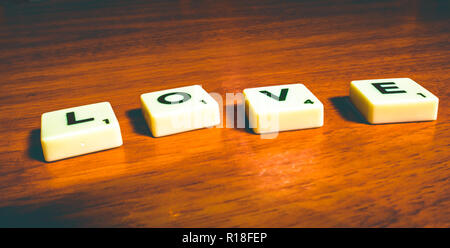 The word love spelled out in scrabble pieces - Stock Photo