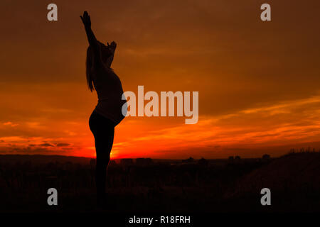 Silhouette of pregnant woman with arms outstretched enjoys spending time outdoor.Toned image. - Stock Photo