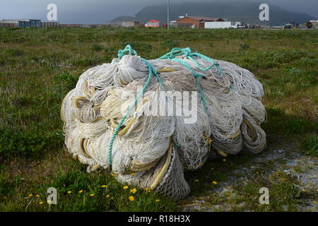 A new commercial fishing trawl net bundled and tied up beside on the shore of the Bering Sea in Dutch Harbor, Unalaska, Alaska, United States. - Stock Photo