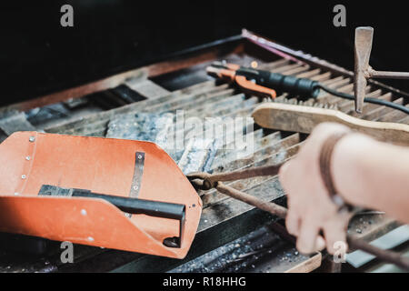 Asian engineering student doing metal work in workshop class using metal hammer to hit the steel after welding. - Stock Photo