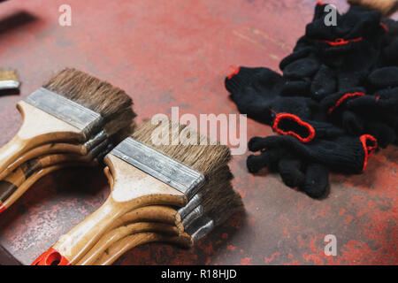bunch of paint brush and glove on the red metallic workbench in workshop room - Stock Photo