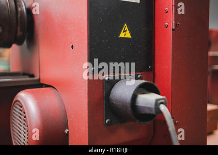 High voltage warning sticker at the back of a power tool in workshop - Stock Photo