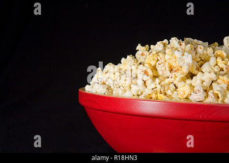 Large red wooden bowl of popcorn isolated on black background. - Stock Photo