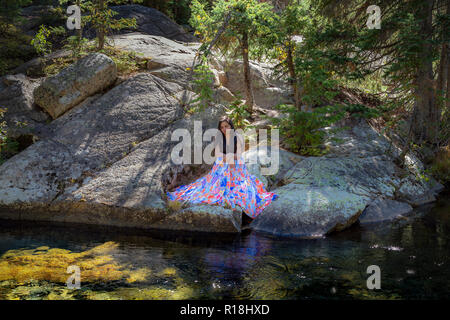 Beautiful young dark-haired woman in pretty dress, sitting on rocks by a river - Stock Photo