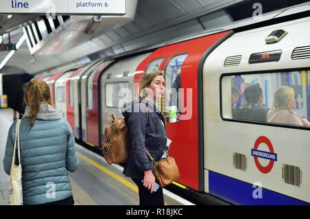 London, England, United Kingdom. Passengers awiting the arriveal of a Central Line underground (subway) train at the Oxford Circus Station. - Stock Photo