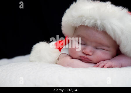 Infant Baby girl posing while sleeping in some with Santa hat and others with blanket.  Also one with angel wings and another in metal bath tub crying. - Stock Photo
