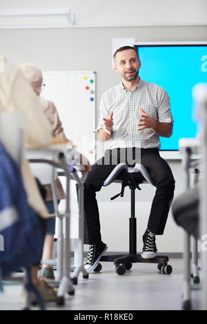 Young teacher in casualwear siting on chair in front of audience and introducing new topic to students - Stock Photo