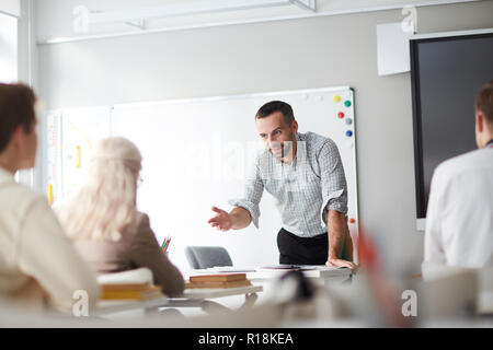 Confident teacher commenting one of students answer while explaining new topic - Stock Photo