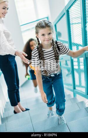 high angle view of schoolgirls going upstairs with teacher at school corridor - Stock Photo