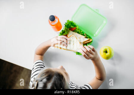 top view of schoolgirl eating sandwich from lunch box - Stock Photo