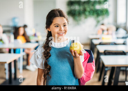 smiling little schoolgirl with green apple at school cafeteria - Stock Photo