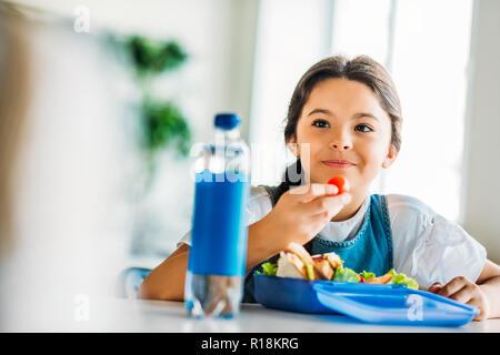 happy little schoolgirl eating lunch at school cafeteria - Stock Photo