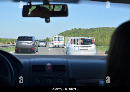 Driving on a highway with other vehicles and an ambulance car in front of him - Stock Photo
