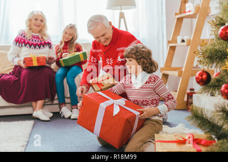 grandparents and kids with gift boxes spending time together on christmas - Stock Photo
