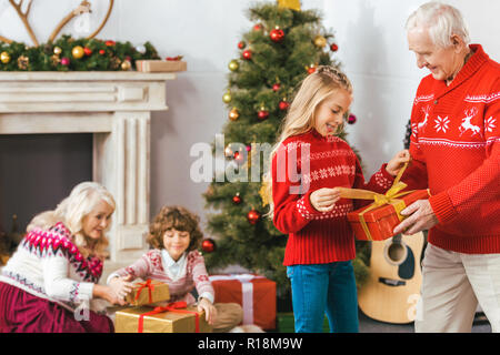 grandparents and adorable kids with gift boxes spending time together on christmas - Stock Photo