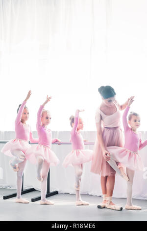 young woman teaching adorable kids dancing in ballet school - Stock Photo