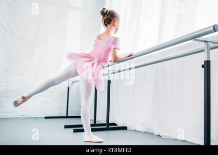 cute little ballerina in pink tutu practicing in ballet studio - Stock Photo