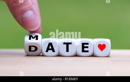 Hand is turning a dice and changes the word 'Mate' to 'Date' - Stock Photo