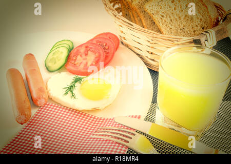 Breakfast on a table, fried egg in a heart-shaped fried sausages, fresh sliced vegetables cucumbers and tomatoes, juice, sliced bread, knife and fork, - Stock Photo