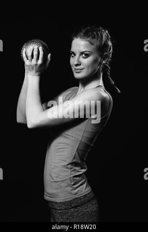 Beautiful young woman is exercising with medicine ball. - Stock Photo