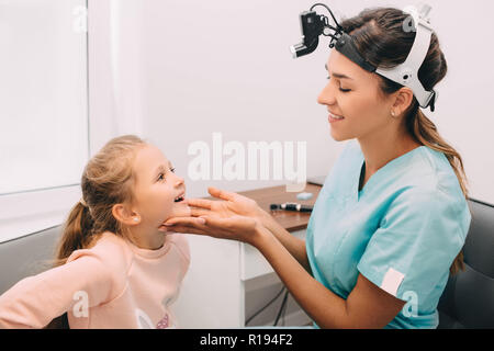 ENT doctor examining mouth of little girl at clinic - Stock Photo