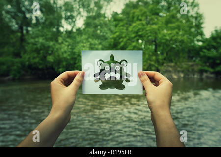 Viruses and environmental pollution cause of genetic mutation and heritable dna damage as woman hands holding a paper sheet with monster hybrid symbol - Stock Photo