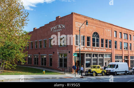ASHEVILLE, NC, USA-10/25/18: Pack's Tavern sets on Spruce St. at Court Plaza, at has an antique truck setting in front, advertising the establishment. - Stock Photo