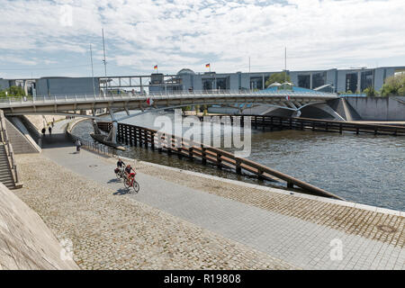 BERLIN, GERMANY - JULY 13, 2018: People walk on Kronprinzenbrucke bridge over Spree river in Mitte central city district. Reichstag and government bui - Stock Photo