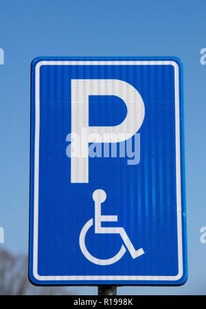 Sign in a car park indicating a parking space for disable drivers - Stock Photo