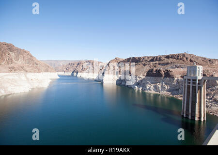 View of Lake Mead  behind Hoover Dam and the water towers. The cliffs discoloration shows how much Lake Mead has receded in level - Stock Photo