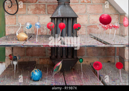 Christmas baubles left to dry up on a wood-burning stove . Unique hand-made xmas ornaments in small manufactory in Ketrzyn, Poland. 27 December 2016. - Stock Photo
