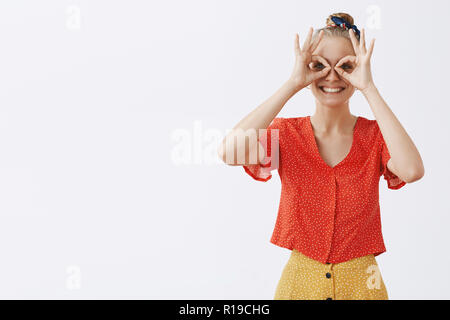 Inner kid wants play. Childish and playful good-looking happy blond female friend in vintage stylish red blouse and skirt, showing zero or okay gestur - Stock Photo
