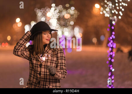 Young girl holding sparklers for christmas during winter alone in the park - Stock Photo