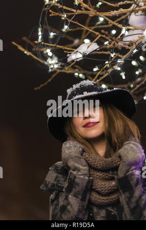 Young girl standing in front of Christmas tree lights at night with snowflakes falling, snowing - Stock Photo