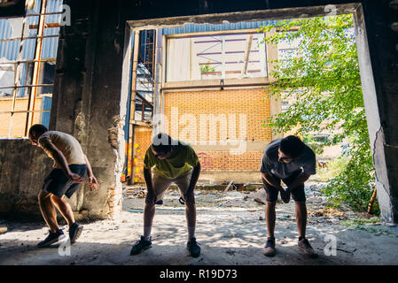 Three young friends training parkour while jumping each other - Stock Photo