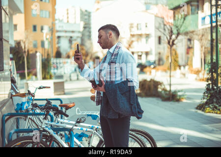 An urban businessman is outside on the city square, standing next to his bike and taking pictures in the mirror of the buildings - Stock Photo