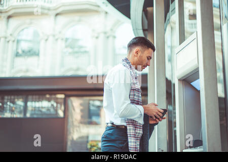 Young businessman is in the city, standing next to the automated teller machine - Stock Photo