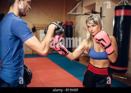 Female kickboxer in gloves practicing hand punch with male personal trainer in pads, workout in gym. Woman boxer on training, kickboxing practice - Stock Photo