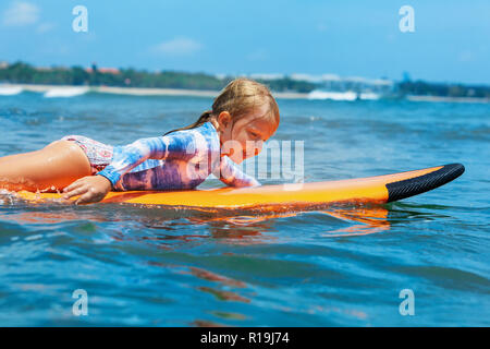 Happy baby girl - young surfer paddle on surfboard with fun on sea waves. Active family lifestyle, kids outdoor water sport lessons, swimming activity