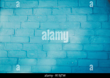 Abstract background texture of a wall. Plastered old brick wall, shabby uneven surface with whitewashing. Painted surface of the house wall.