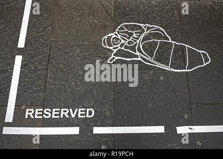 Edinburgh, Royal Mile,  10th November 2018. An anonymous street artist makes a statement about homelessness in the form of a 'reserved' area with line markings in the shape of a homeless person on The Royal Mile, Edinburgh, Scotland, UK. - Stock Photo