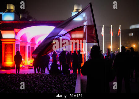 Warsaw, Poland. 10th Nov, 2018. A man seen holding a polish flag next to the tomb of Unknown Soldiers during the Unveiling of a new statue of the Former Polish President Lech Kaczynski at Pilsudskiego Square on the day before the centenary independence day. Credit: Omar Marques/SOPA Images/ZUMA Wire/Alamy Live News - Stock Photo